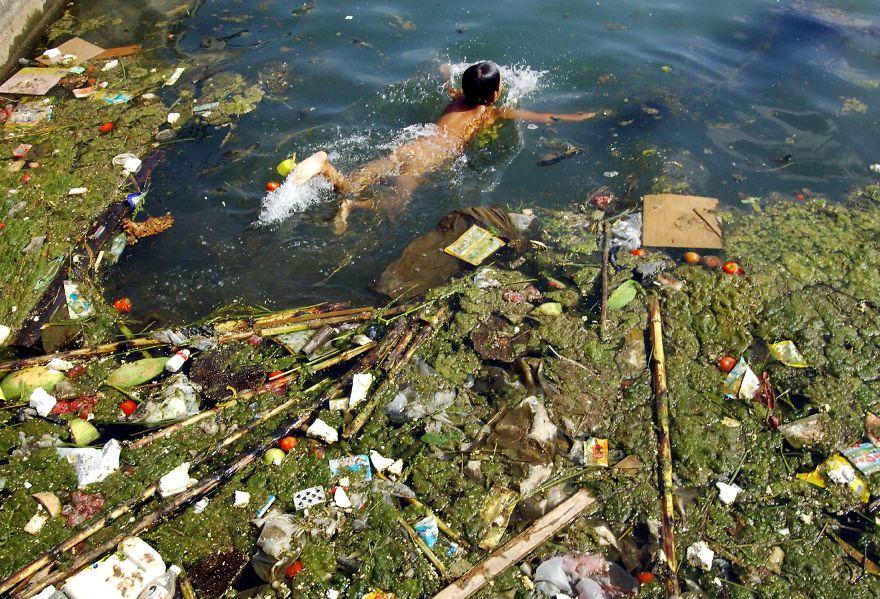 criança a nadar num reservatório de água poluido china